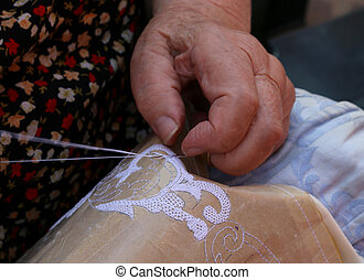 Hands of an elderly woman embroidering a lace with tombolo...