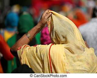 elderly woman with headscarf and hand during a religious...