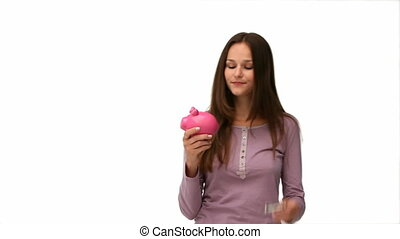 Woman putting money into piggybank against a white...