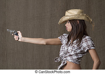 Stand off - Young brunette cowgirl aiming a small gun to the...
