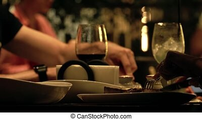 Unknown people eating steaks in a restaurant, table close-up...