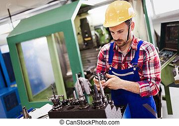 modern industrial machine operator working in factory -...