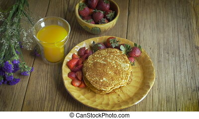 High angle dolly of healthy breakfast of strawberries, pancakes, and juice