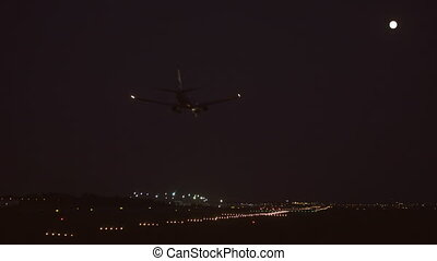 Jet landing at night against full moon, bottom view - Bottom...