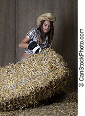 Hard working - Young cowgirl lifting a bale of straw