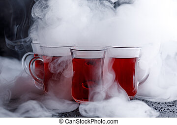 red cocktail with ice vapor. red cold tea with steam on a...