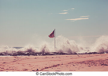 American Flag on Jetty - An American flag stands in the surf...