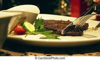 Eating juicy steaming steak in a restaurant, plate close-up...