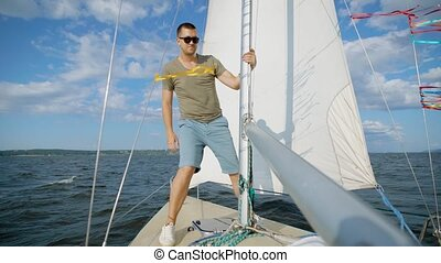 Male adventurer posing on modern sailboat looking away in...