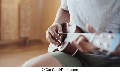 Person playing on ukulele guitar inside - Crop shot of man...