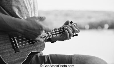 Person playing on little ukulele guitar - Black and white...