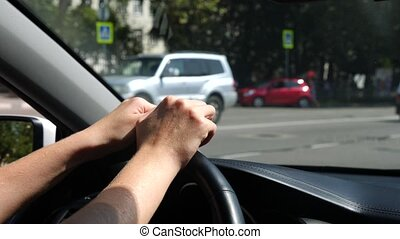 close-up of hands on the steering wheel of a car. sun glare....