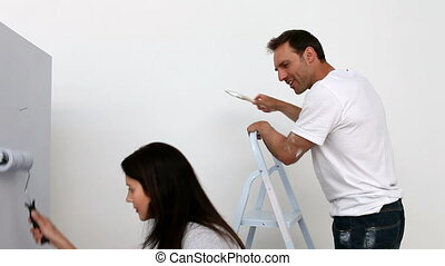 Couple painting a wall in white in a bedroom