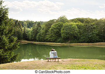 Senior couple on a walk at the lake hugging. - Beautiful...