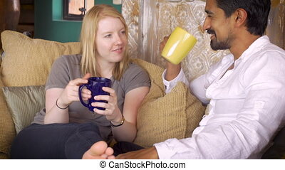 A couple drink coffee together and carry on a joyful...