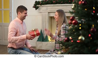 Man giving Christmas present to his girlfriend - What a...