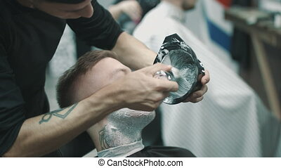 Barber putting some shaving cream on a client. - Shaving the...