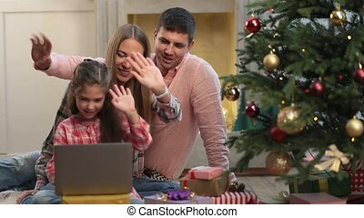 Christmas family chatting on internet with laptop - Cheerful...