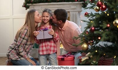 Loving parents kissing daughter on Christmas eve