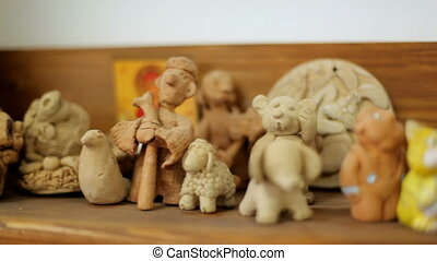 Clay toys and souvenirs stand on the shelf. Handmade folk art