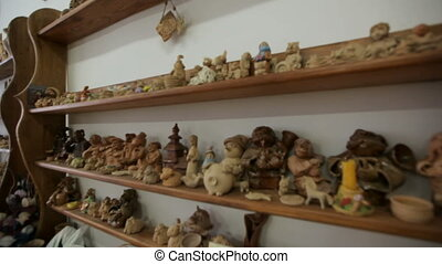 Workshop of folk art. On the shelves are clay products, souvenirs, dishes.Clay toys and souvenirs stand on the shelf. Handmade folk art