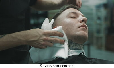 Barber wipes off with a napkin the face of the client. -...