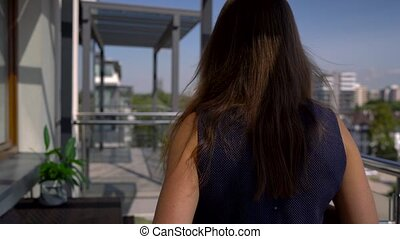 Woman relaxing on balcony holding cup, drinking coffee or...
