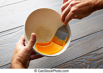 creamy carrot cream painted on white bowl while chef...