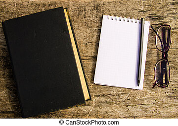 Old closed book, glasses, notepad and pen on wooden background
