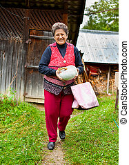 Old rural woman with pumpkin outdoor - Portrait of an old...