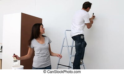 Lovely couple painting their room in white together