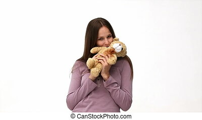 Happy woman playing with a teddy bear isolated on a white...