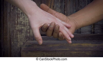 White and black hands lovingly embrace in front of a...