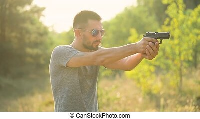 Young man is shooting from a gun, close up. Slow motion -...