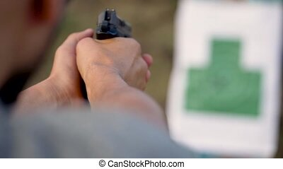 Young man is shooting from a gun at the target, close up....
