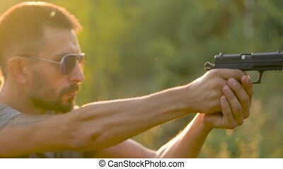 Young man is shooting from a gun, close up. Shooting...