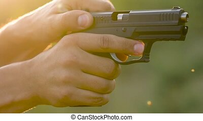 Gun is shot close-up. Man is shooting from a gun