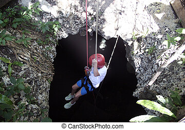 Girl rapelling into cave - Girl rapelling into dark cave in...