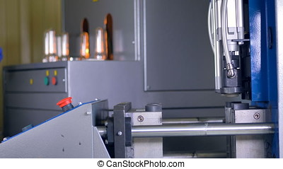 A blow molding machine at work in high speed. - A worker...