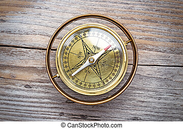 vintage brass compass isolated on aged wooden table