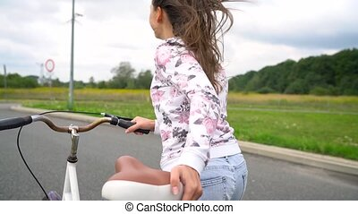 Woman laughing and running down the street with a bicycle -...