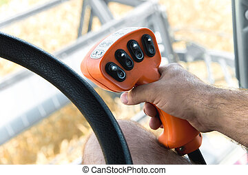 The man's hand holds the control lever of the grain harvester