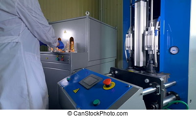 A worker in a lab coat makes preforms into large PET...