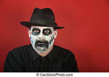 Man in scary makeup - Man with face covered in makeup for...