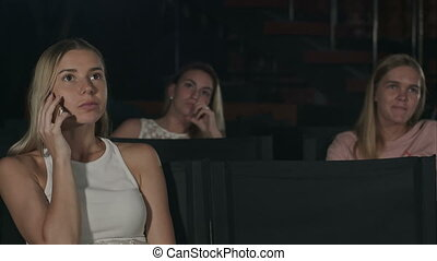 Young woman on the phone during movie at the cinema. Close...