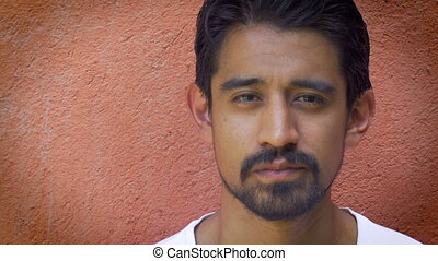 Portrait shot of a young handsome latino man against an...