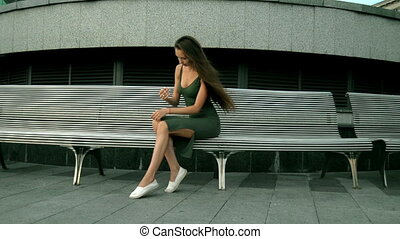 sexy slender girl with long hair sitting on a bench and...