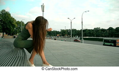 beautiful young lady with long hair sitting on a bench and...