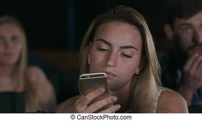 Shot of a beautiful young female texting during movies at...