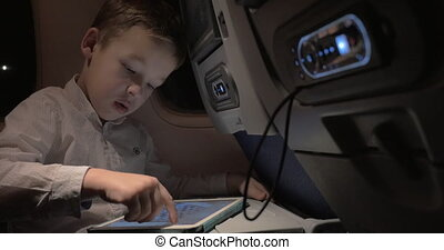 Kid traveling by air and passing time with pad chess game -...
